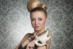 Stunning actress girl with mask. Stunning blonde woman with elegant hair-style and necklace posing like a actress with decorated mask in the hand Stock Photography