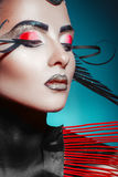 Stunning adult female with red and black stripes in studio Royalty Free Stock Photos