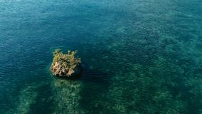 Stunning aerial drone image of a colorful seabed reef with a cliff rock standing out of water in calm weather flat seas and. Incredible colorful sea ocean bed stock photo