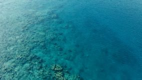 Stunning aerial drone image of a a small fishing boat entering an a sea ocean anchorage in a channel next to a coral reef in royalty free stock photos