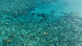 Stunning aerial drone image of a a small fishing boat entering an a sea ocean anchorage in a channel next to a coral reef in stock images