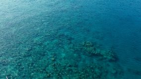 Stunning aerial drone image of a a small fishing boat entering an a sea ocean anchorage in a channel next to a coral reef in stock photography