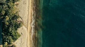 Stunning aerial drone minimal geometric image of a remote tropical sea ocean shore with sandy beach lush rainforest jungle and. Crystal clear azure blue water stock photos