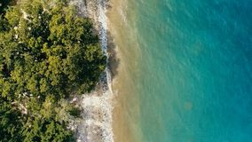 Stunning aerial drone minimal geometric image of a remote tropical sea ocean shore with sandy rocky beach lush rainforest jungle. And crystal clear azure blue royalty free stock images