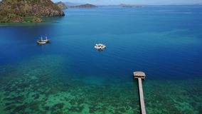 Aerial view of turquoise water in Labuan Bajo. Stunning aerial view footage of turquoise sea water with pier and boat in Labuan Bajo at Flores Island an island stock video