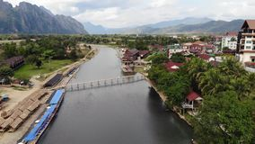 Stunning aerial view of two tourists who are kayaking on river that runs through the village of Vang Vieng. Vang Vieng. Stunning aerial view of two tourists who stock video