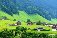 Stunning alpine landscape in canton Uri, Switzerland. Beautiful view of idyllic mountain scenery in the Alps with traditional chalets and farm in green alpine Stock Photography