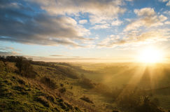 Stunning Autumn sunrise over countryside landscape Stock Photos