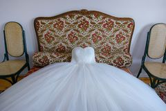 Stunning ball gown wedding dress spread on a small sofa. Elegant bridal accessory, the white dress as part of a traditional Western wedding routine, ready for Royalty Free Stock Image
