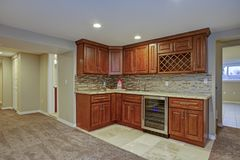 Stunning basement interior with wet bar. Stunning basement interior boasts a nice wet bar composed of wood shaker cabinets with granite countertop and a mosaic Stock Images