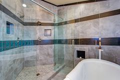 Stunning bathroom with a freestanding tub. Stunning bathroom boasts an oversized glass shower and white freestanding tub lined with gray marble tiled surround royalty free stock image
