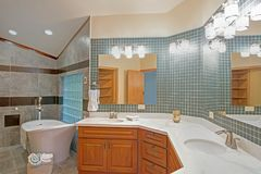 Stunning bathroom with a freestanding tub. Stunning bathroom with light wood vanity paired with calcutta marble countertops and large frameless mirror. The stock photography