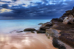Stunning beach and coastal rocks before sunrise Royalty Free Stock Image