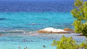 A glorious Greek beach with a small rock for diving in area of Kavourotripes Halkidiki Greece. Stunning beach in Kavourotripes Halkidiki in Greece with blue stock video footage