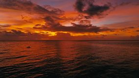 Stunning beautiful aerial drone image of a red tropical sunset above the sea ocean with two man in a canoe fishing.  royalty free stock photo