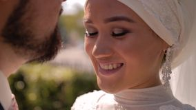 A stunning beautiful girl presses her forehead to her man. She happily smiles with his eyes closed. then he opens his eyes and loo. Ks at his husband. Nice close stock video