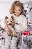 Stunning beautiful little girl with long blond hair lies on the bed linen in the printing dogs and lies next to her dog Yorkshire Royalty Free Stock Photography
