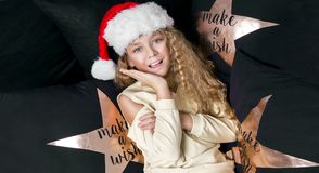 Stunning beautiful little girl with long blond hair lying on a bed in a Santa Claus hat Stock Photography