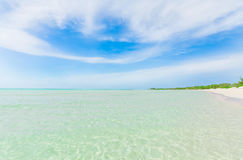 Stunning beautiful view of tranquil turquoise ocean, beach against magic mesmerizing blue sky background Royalty Free Stock Images