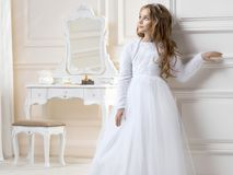 Stunning beauty young girl model in the white communion dress. Stands in an elegant palace Stock Photo