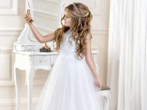 Stunning beauty young girl model in the white communion dress. Stands in an elegant palace Stock Images