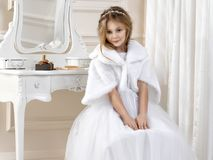 Stunning beauty young girl model in the white communion dress. Stands in an elegant palace Royalty Free Stock Photos
