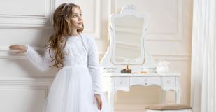 Stunning beauty young girl model in the white communion dress. Stands in an elegant palace Stock Photos