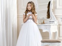 Stunning beauty young girl model in the white communion dress. Stands in an elegant palace Royalty Free Stock Image