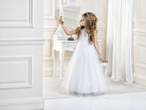 Stunning beauty young girl model in the white communion dress. Stands in an elegant palace Royalty Free Stock Images