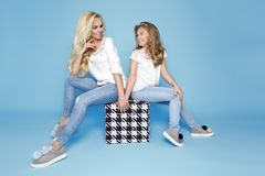 Stunning beauty of a young mother with a cute blonde daughter sitting on a blue background dressed in a jeans stock photo