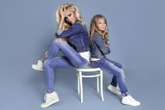 Stunning beauty of a young mother with a cute blonde daughter sitting on a chair on a blue background dressed Stock Photography