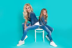 Stunning beauty of a young mother with a cute blonde daughter sitting on a chair on a blue background dressed Royalty Free Stock Photo