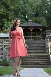 Gorgeous biracial woman poses wearing pink dress in garden Royalty Free Stock Photo