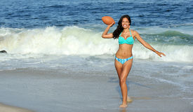 Stunning biracial woman at beach with football Royalty Free Stock Photos