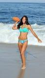 Stunning biracial woman at beach with football Royalty Free Stock Photos