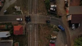 Aerial shot of several cars crossing the railroad jucnction in summer. A stunning bird`s eye view of a jucnction of an asphalt road and a railroad with two lanes stock video footage