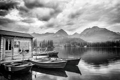 Stunning black and white landscape with cloudy sky, mountains and lake with pleasure boats, Strbske pleso, High Tatras, Slovakia stock photography
