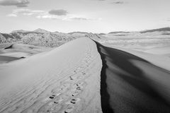 Stunning black and white sand dune with footprints. Stock Photo