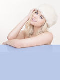 Stunning blond woman in a white winter hat Stock Photography