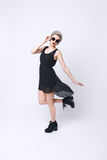 Stunning blond young woman wearing black dress and sunglasses Stock Photo