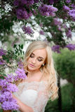 Stunning blonde bride stands with closed eyes stock photography