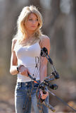 Stunning blonde female archer. Stunning young blonde woman in white tank top and jeans preparing to shoot a compound bow - archery Royalty Free Stock Photography