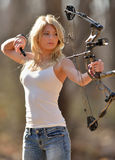 Stunning blonde female archer. Stunning young blonde woman in white tank top and jeans shooting a compound bow - archery - arrow shown leaving bow Stock Photos