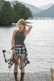 Beautiful young blonde female archer with compound bow. Stunning blonde female Caucasian archer playfully poses with her compound bow near a lake Royalty Free Stock Photo