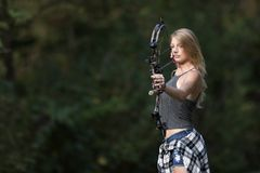Beautiful young blonde female archer with compound bow. Stunning blonde female Caucasian archer shoots an arrow from a compound bow Stock Photo