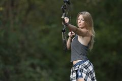 Beautiful young blonde female archer with compound bow. Stunning blonde female Caucasian archer shoots an arrow from a compound bow Royalty Free Stock Photos