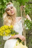 Stunning blonde sexy natural woman swing on a swing on a tree wearing a spring dress. Holding a bouquet of spring Royalty Free Stock Images