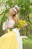 Stunning blonde sexy natural woman swing on a swing on a tree wearing a spring dress. Holding a bouquet of spring Royalty Free Stock Photos