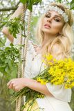 Stunning blonde sexy natural woman swing on a swing on a tree wearing a spring dress. Holding a bouquet of spring Royalty Free Stock Image