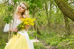 Stunning blonde sexy natural woman swing on a swing on a tree wearing a spring dress. Holding a bouquet of spring Royalty Free Stock Photography